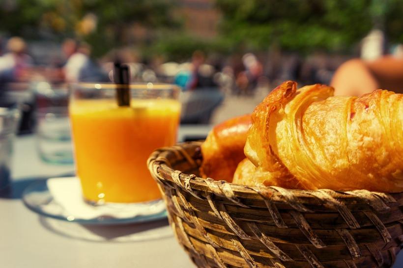 L'image presente un jus d'orange et des croissants, illustration de l'article